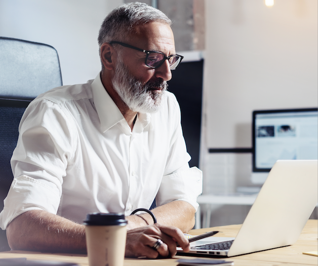 Man looking at pension statements on laptop