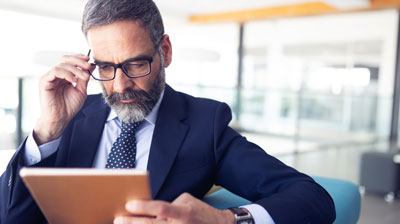 Inquisitive man holding tablet with glasses